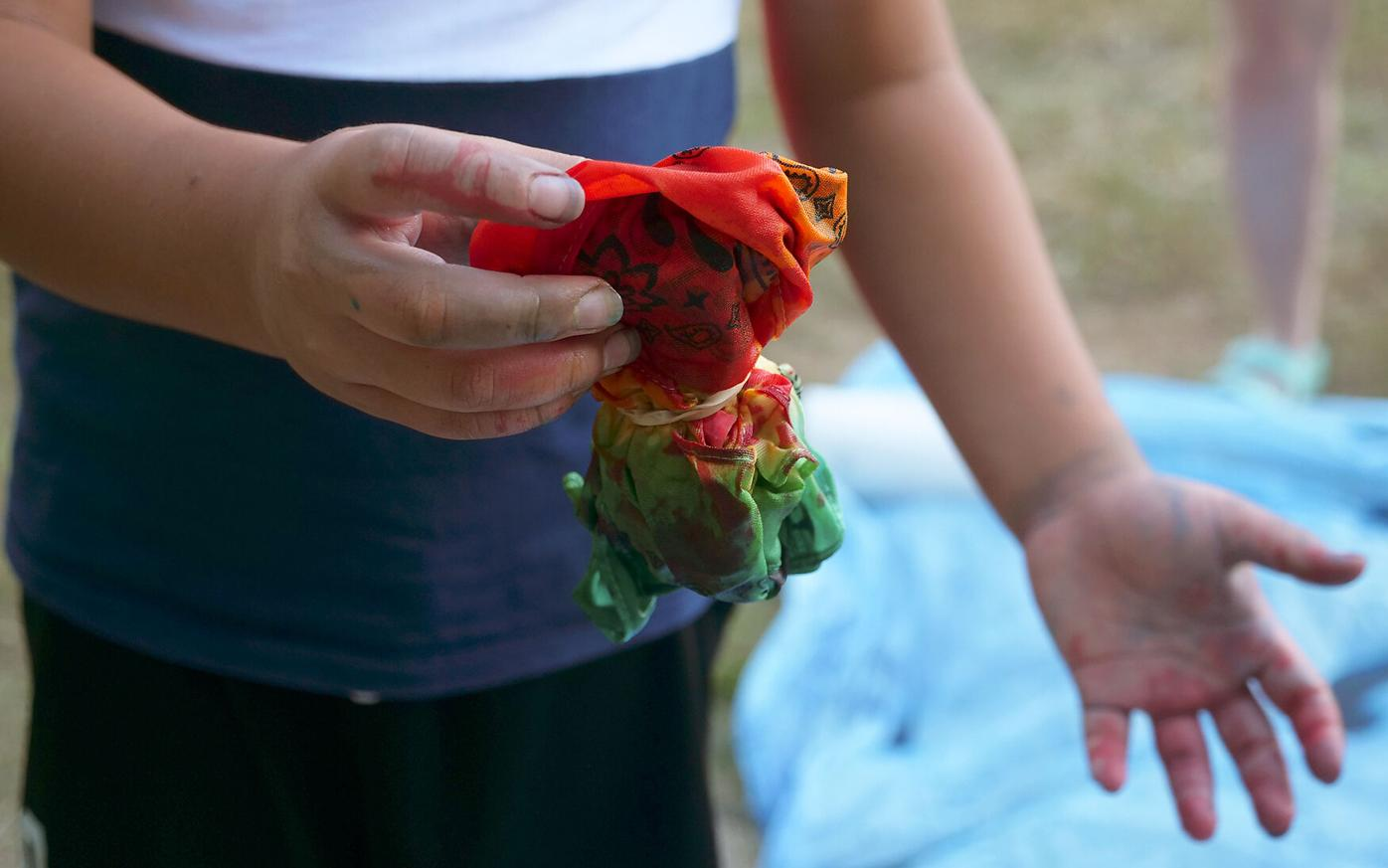 Community members tie-dye shirts with every color