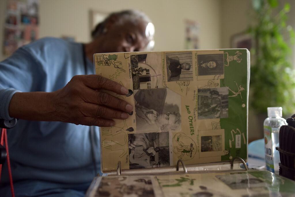 Frances Regina Robinson looks through her high school portrait