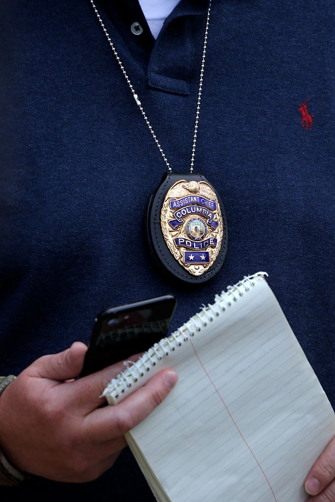 Assistant Columbia Police Chief Jeremiah Hunter grips a notebook and phone while talking to the press