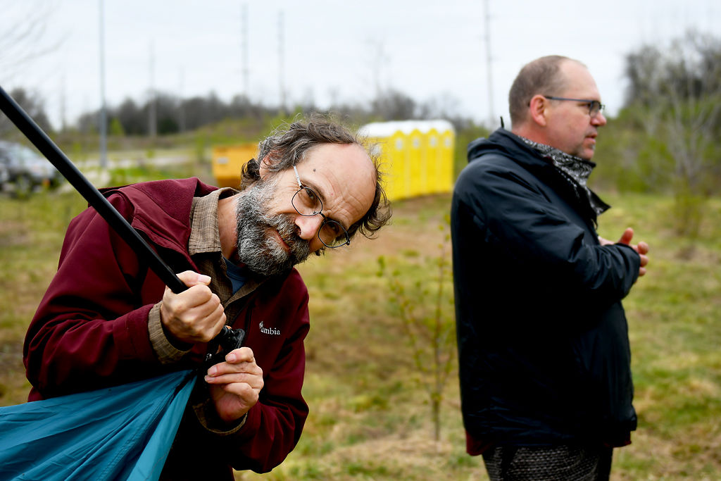 John Trapp, left, takes down a tent as his brother, city council representative Mike Trapp, has a discussion