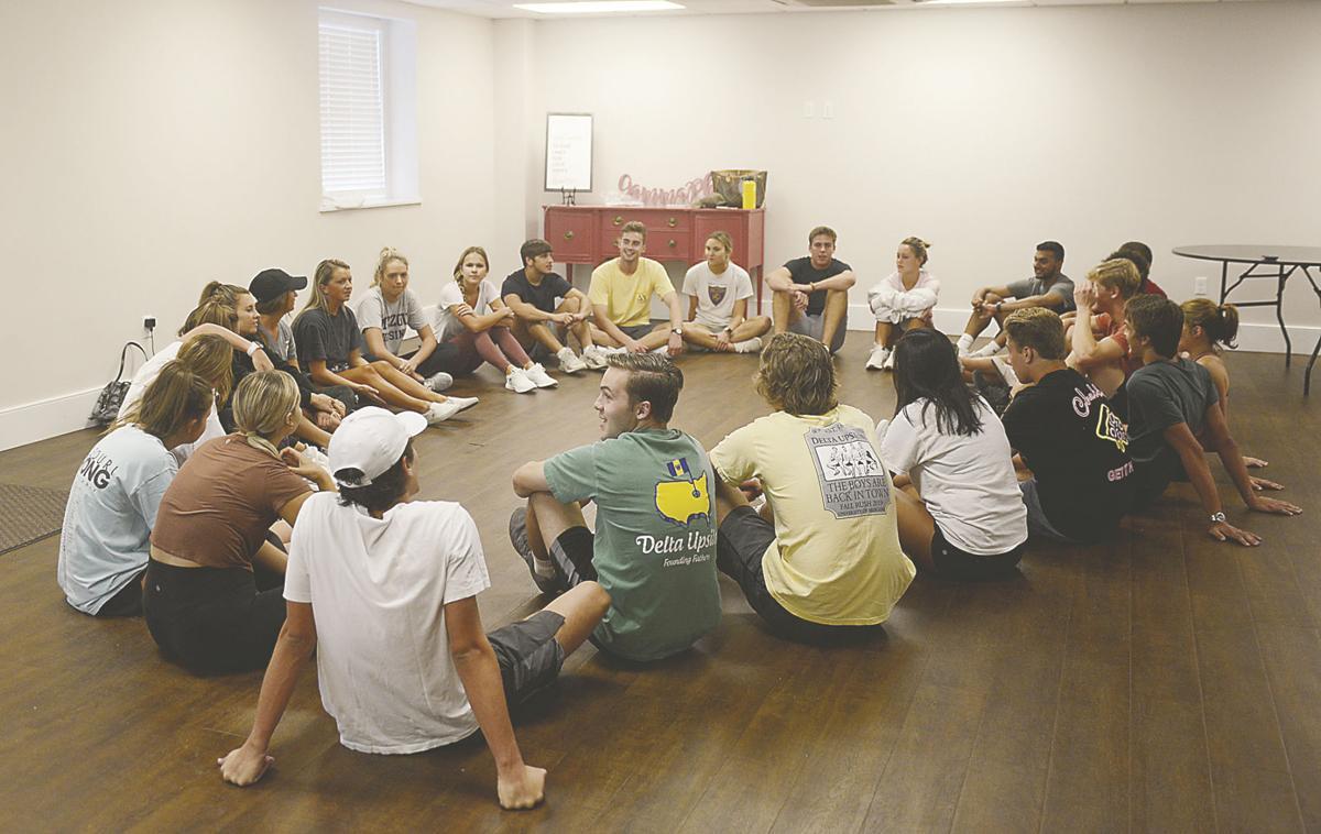 Members of Gamma Phi Beta, Delta Upsilon and Alpha Kappa Lambda sit in a circle
