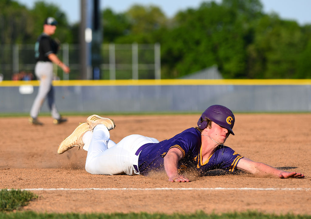 Hickman outfielder Gage Slaughter slides into third as an attempt to tag the bag