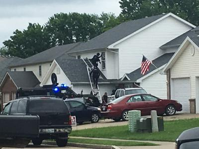 SWAT members use a ladder to reach the roof and a window of a home
