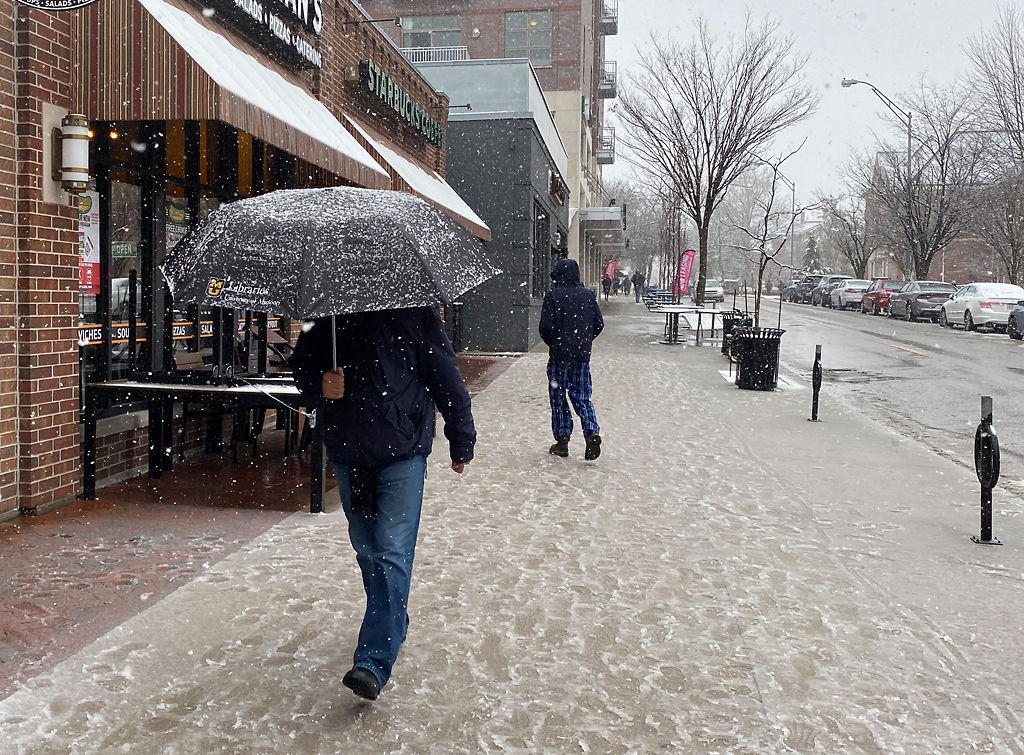 A person uses an umbrella as a shield against the snow
