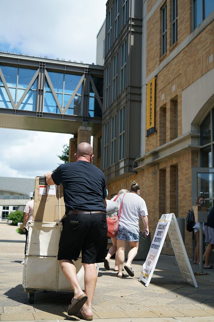 Matt Gamertsfelder pushes a trolley with daughter Maddie toward an MU residence hall