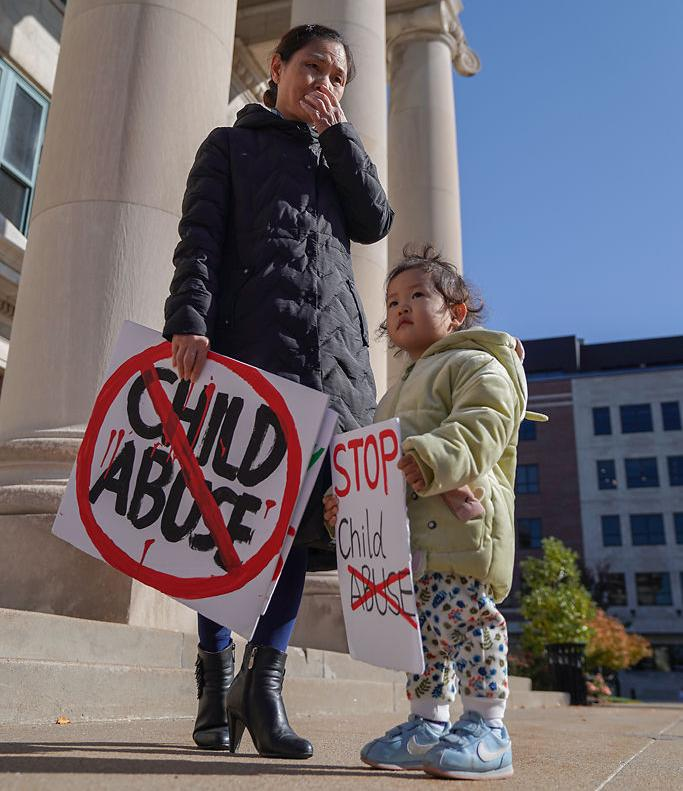 Ying Su and her granddaughter Grace, 2, stand Tuesday in front of the Boone County Courthouse.