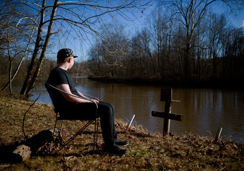 Gary Edge's son poses for a portrait next to a lake in Versailles, Missouri