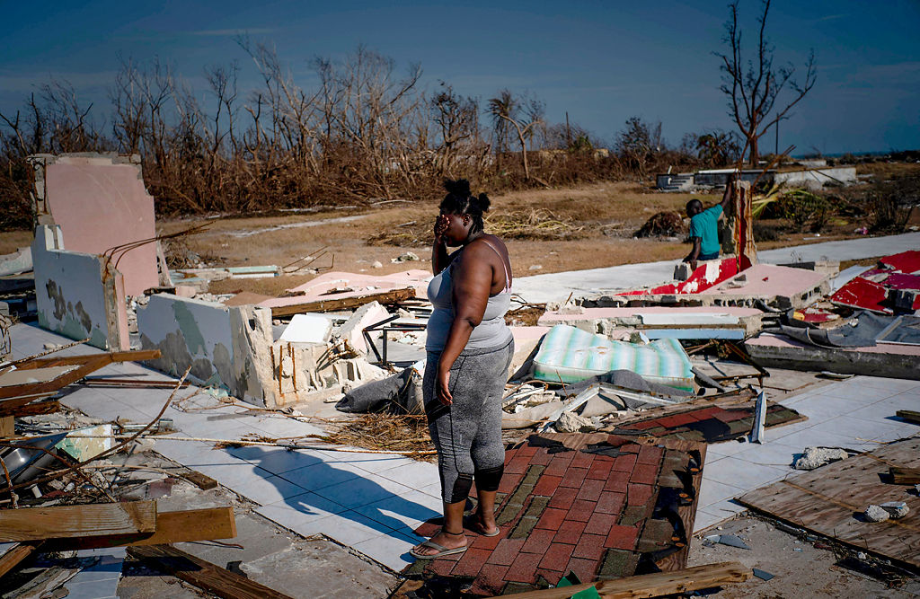 A woman is overcome as she looks at her house destroyed by Hurricane Dorian