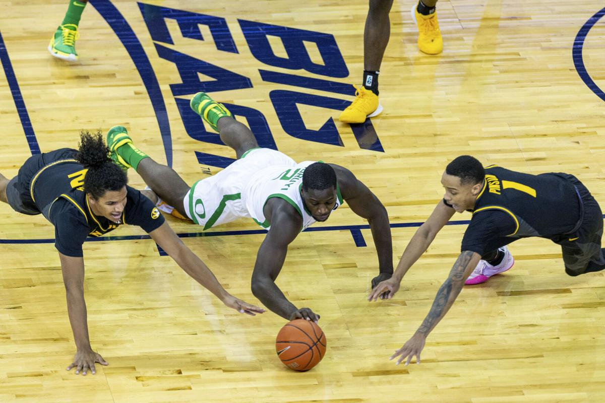 Missouri guard Dru Smith (12), Oregon forward Eugene Omoruyi (2), and Missouri guard Xavier Pinson (1) go after a loose ball during the first half of an NCAA college basketball game, Wednesday, Dec. 2, 2020 in Omaha, Neb.