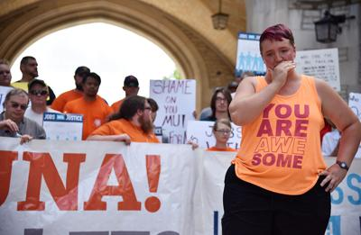 Kayla Payne tears up while telling a story about her mom during a rally for wage increases