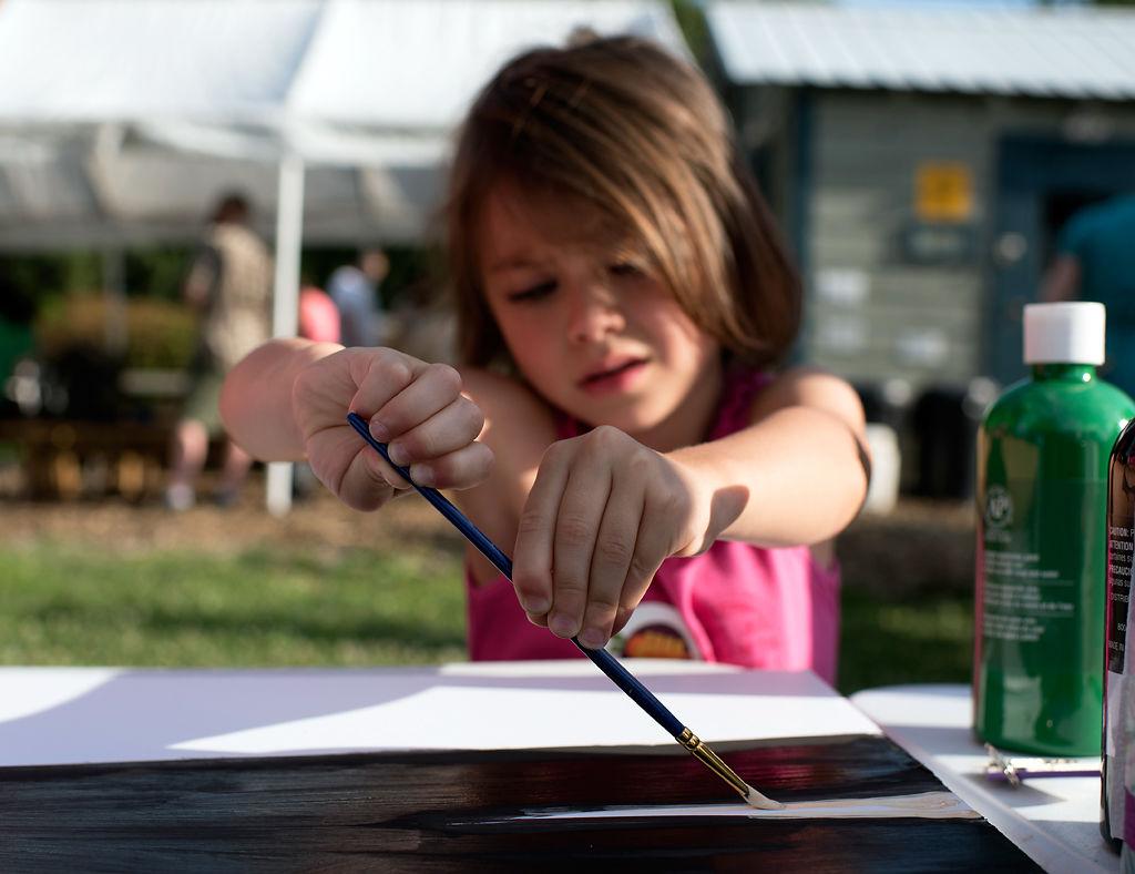 Hannah Fansler, 4, paints part of the mural