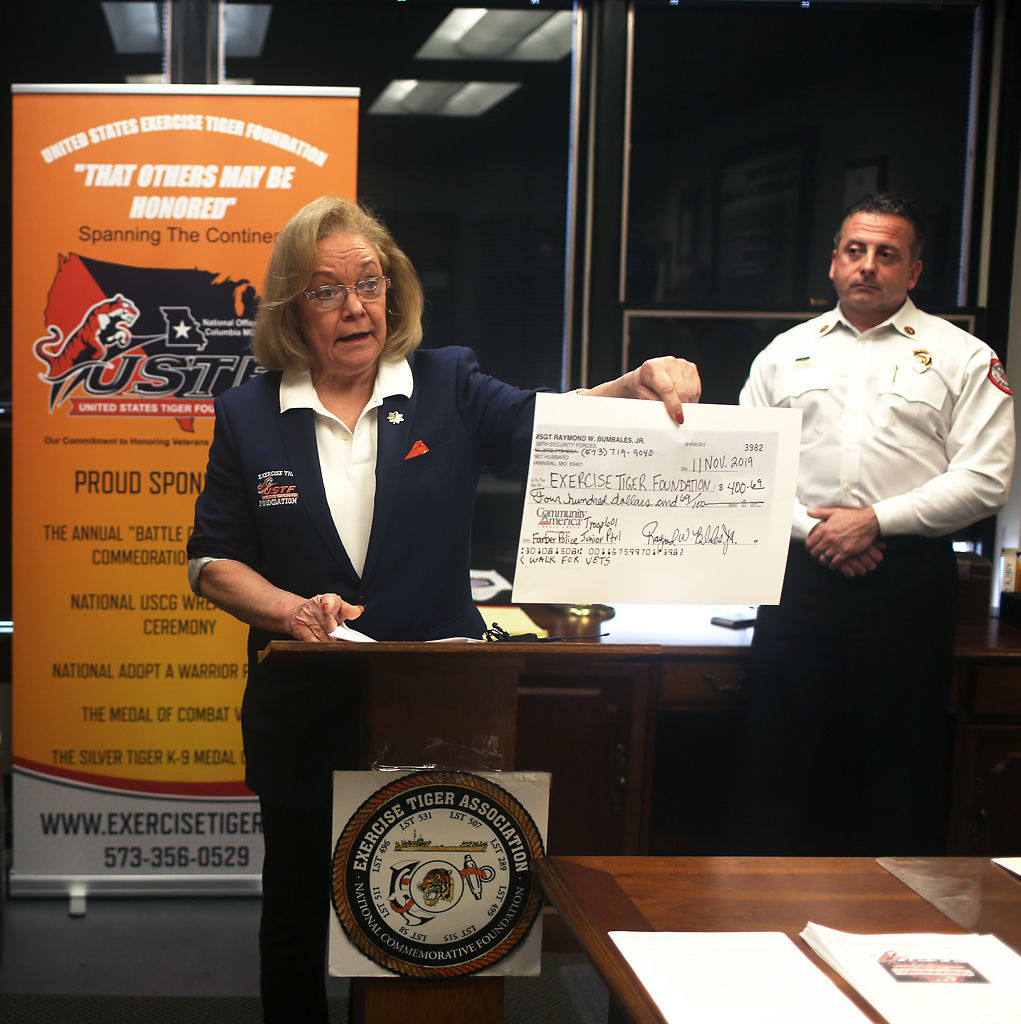 National Executive Director of the USTF, Susan Haines, center, holds up a check from Junior Police Troop 601