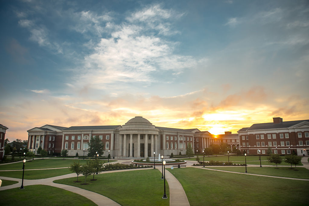 The sun rises over Shelby Hall at the University of Alabama