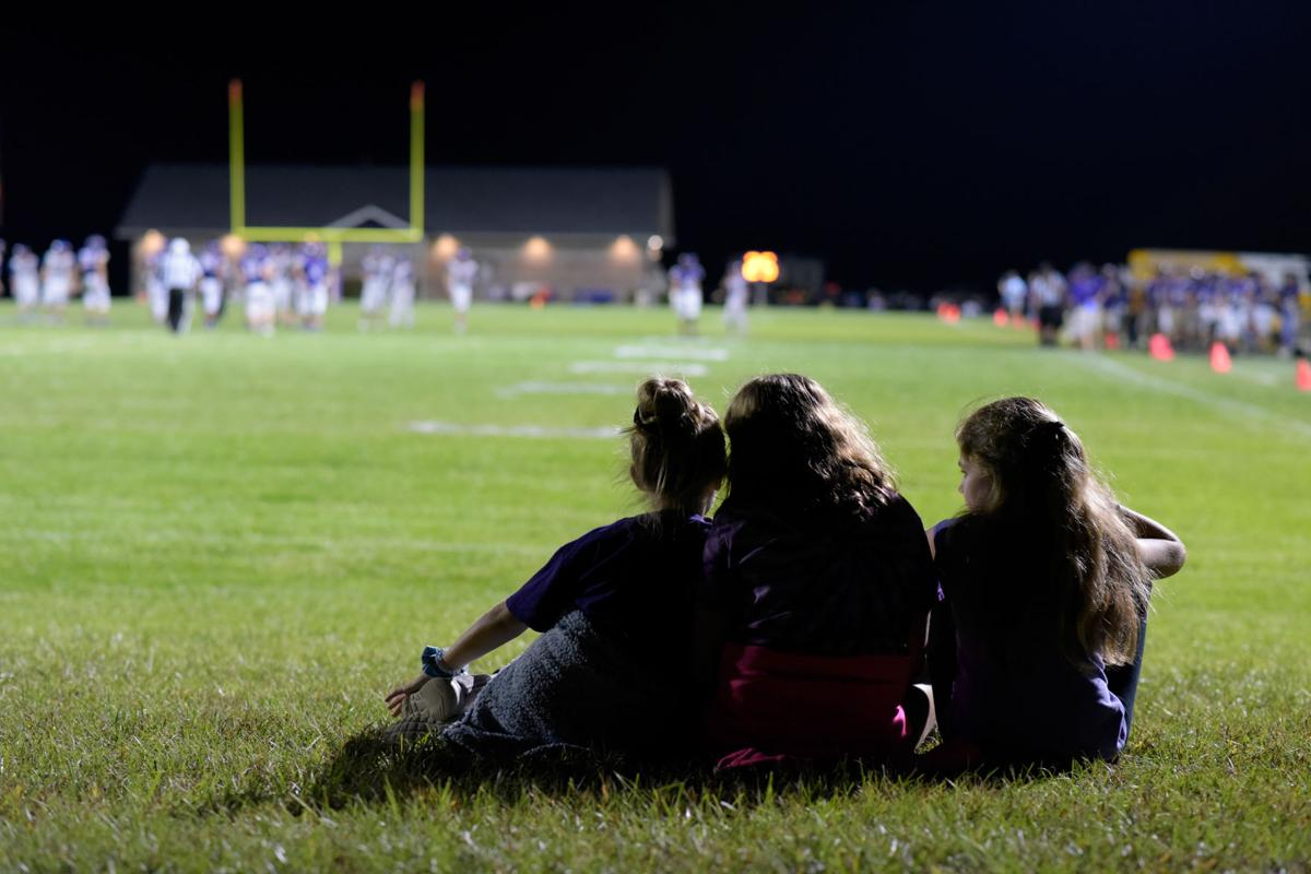 From left to right, Bella Abell, Keatyn Hogf and Ava Gilo, all 11 years old, watch a Hallsville High School varsity football game