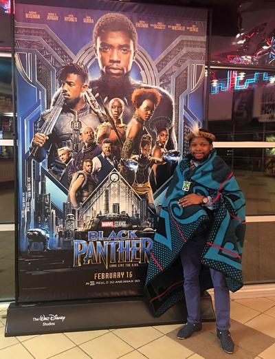 Velaphi Thipe stands next to a poster for Black Panther