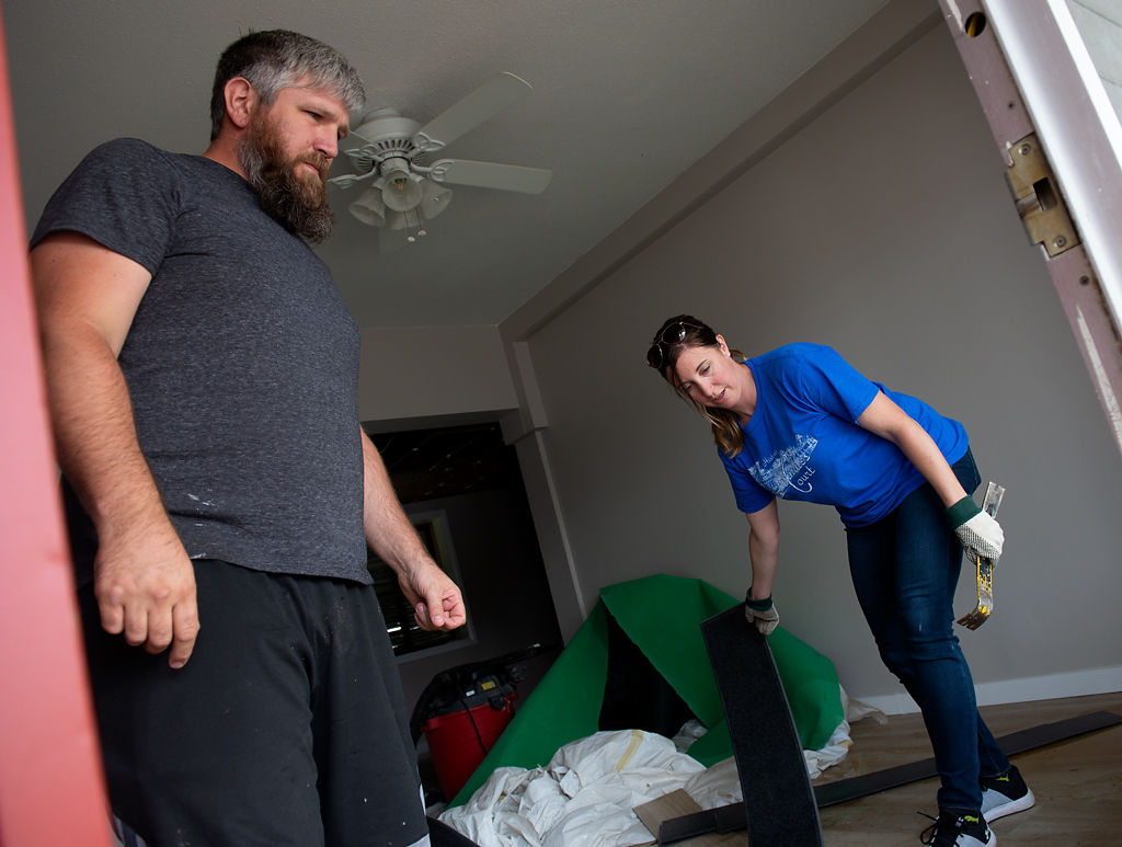 Jeremy and Jennifer Hart clear out waterlogged flooring from one of the rooms