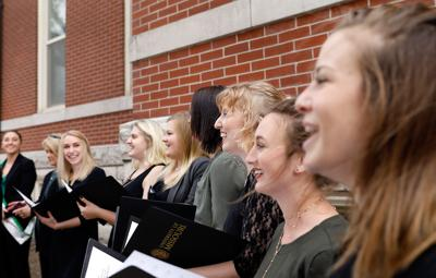 The Naturelles a cappella group smiles at an applauding crowd
