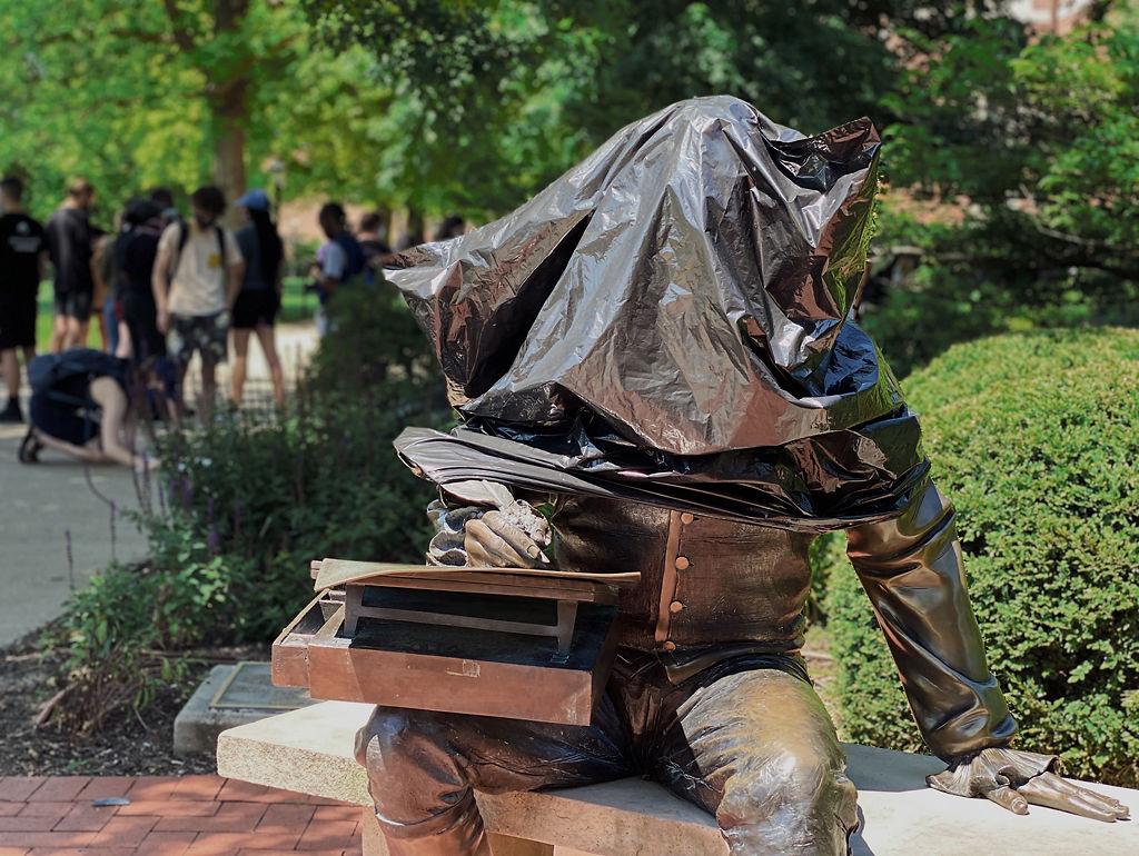A black plastic bag covers the head of the statue of Thomas Jefferson