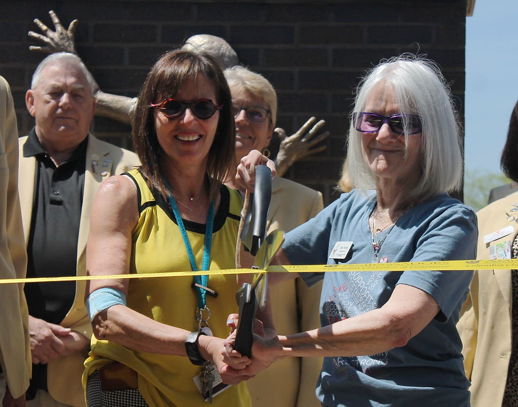 Dasi Schlup, left, and Sally Silvers, cut the golden ribbon