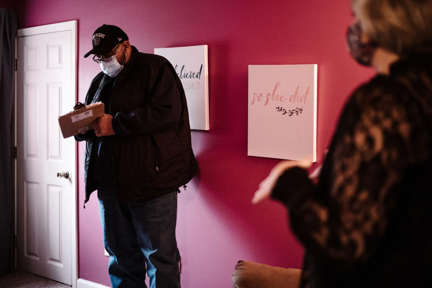 Kevin Gaines, left, calculates a quote to transport Misty Philips', right, furniture
