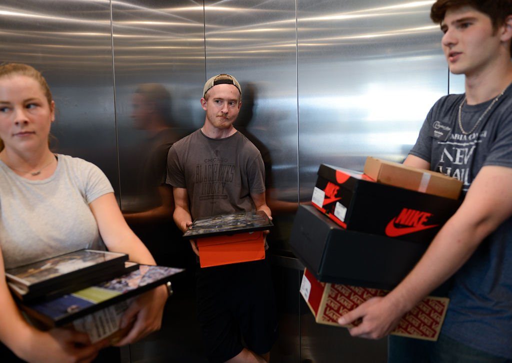 From left, Nicole Emmons, Mason Mueller and Kyle Rolfes, help their friend during move in day for residents of New Hall