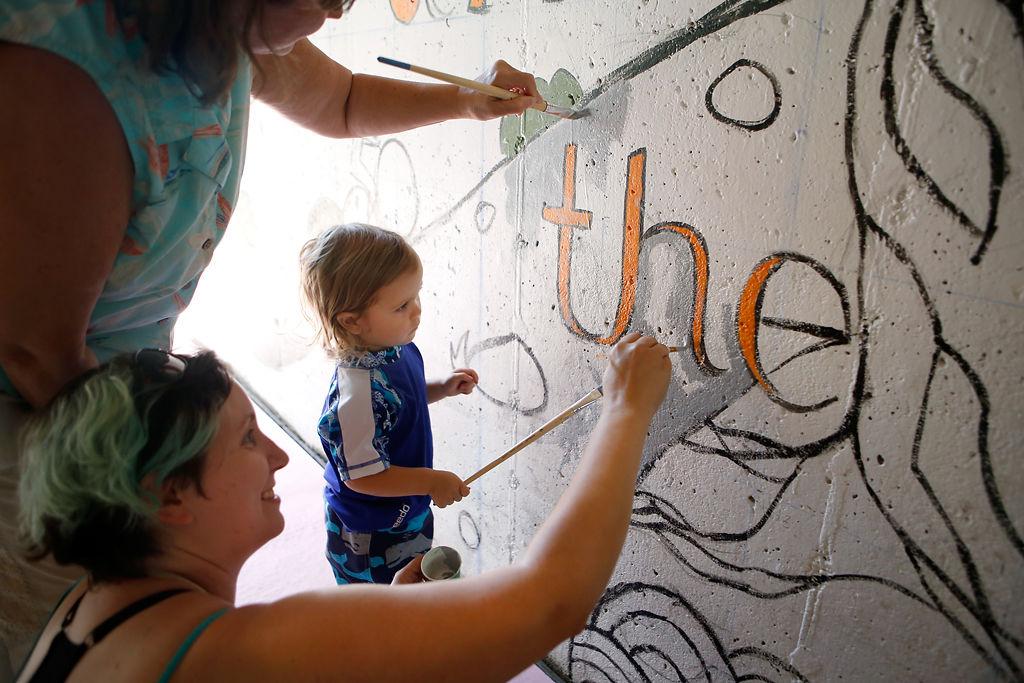 Volunteers paint a mural