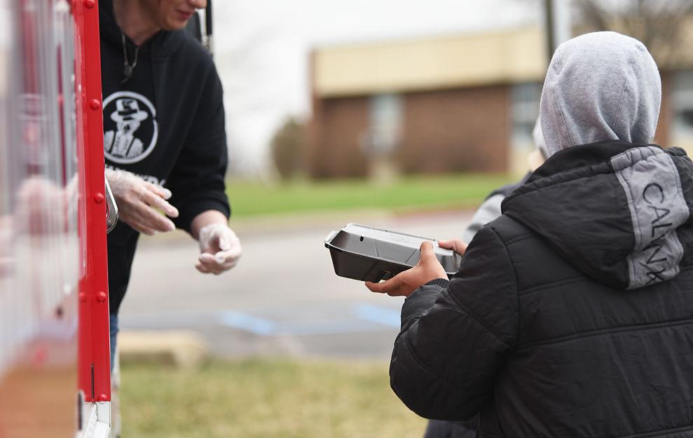Avion Pope, 14, picks up a box lunch from Sara Reichert