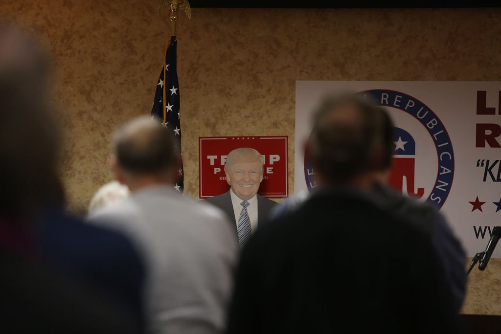 A cardboard cutout of Donald Trump stand in front of Lee County republicans