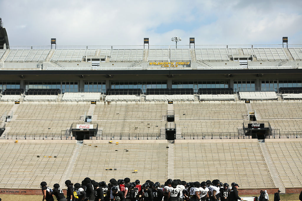 The Missouri football team huddles together at the beginning of spring football practice