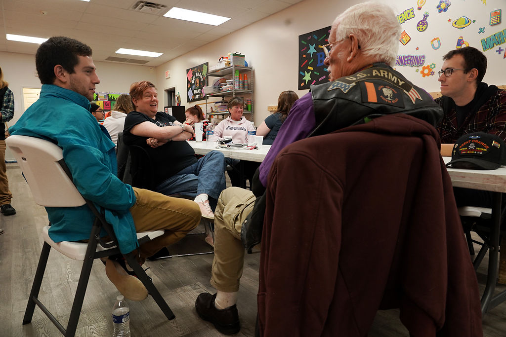 Bryce Homen and Mindy Megas-Loucks speak with other members