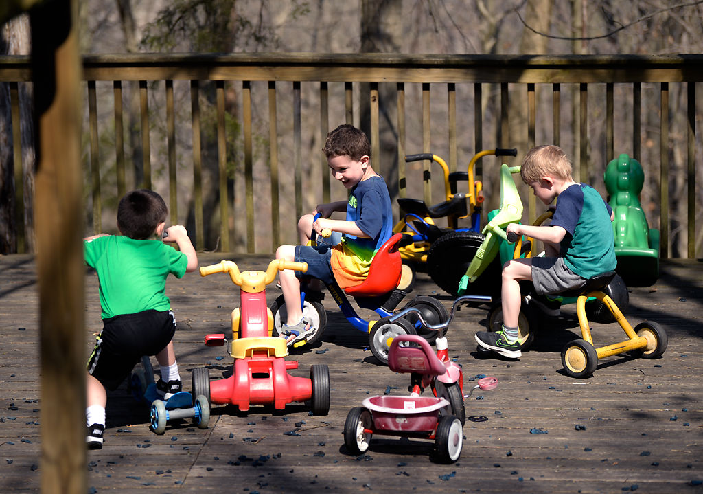 Wyatt Comes, Isaac Suttner, and Asher Simons, play with tricycles