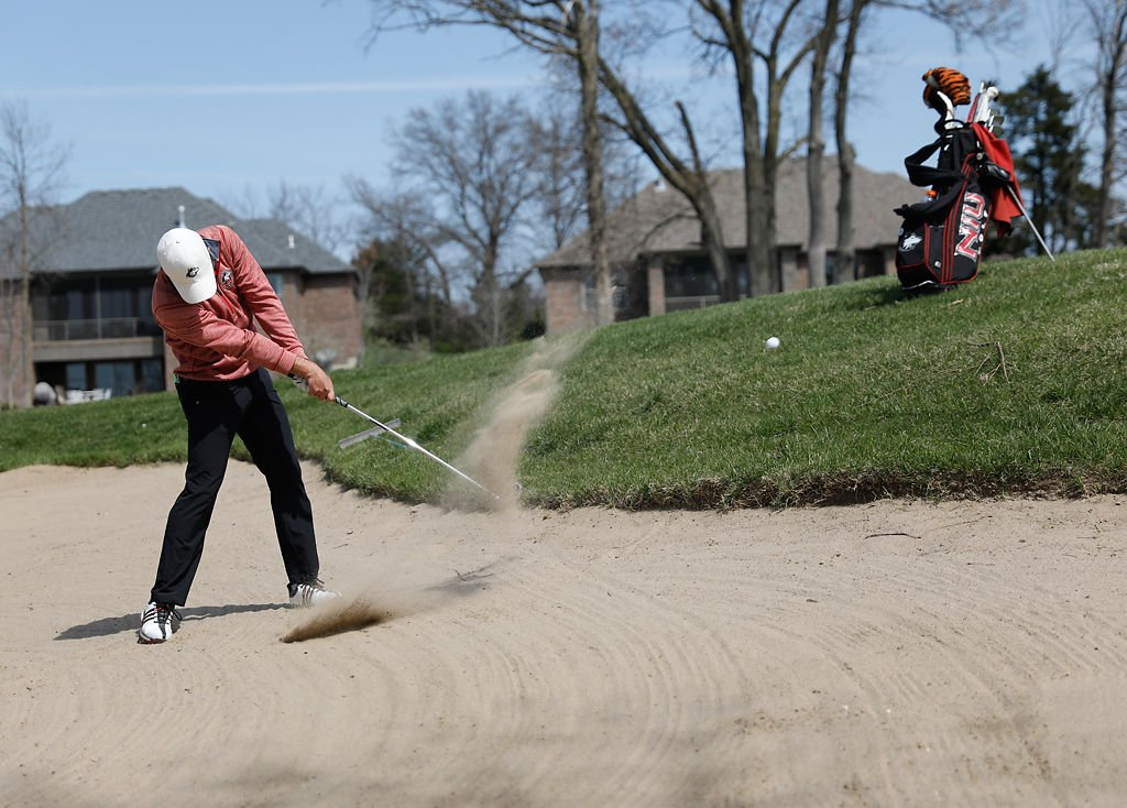 Northern Illinois University golfer Salvador Rocha hits a ball out of a sand trap