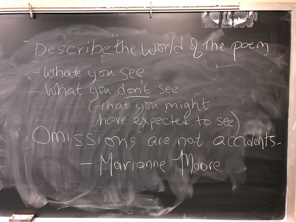 A blackboard displays techniques to analyze world-building in a poem