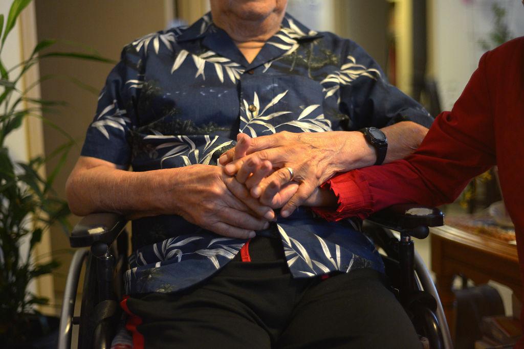 Amador Molina holds his wife Alicia Molina's hand
