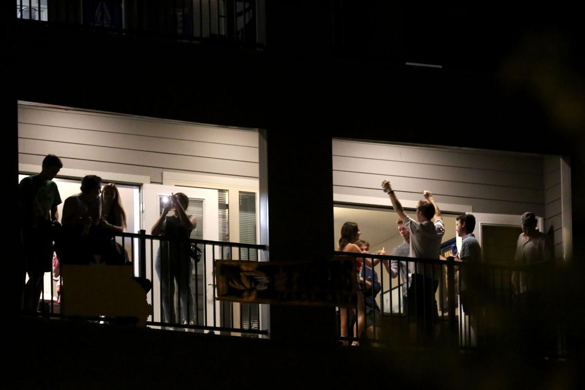 Partiers congregate on the balcony of a downtown apartment