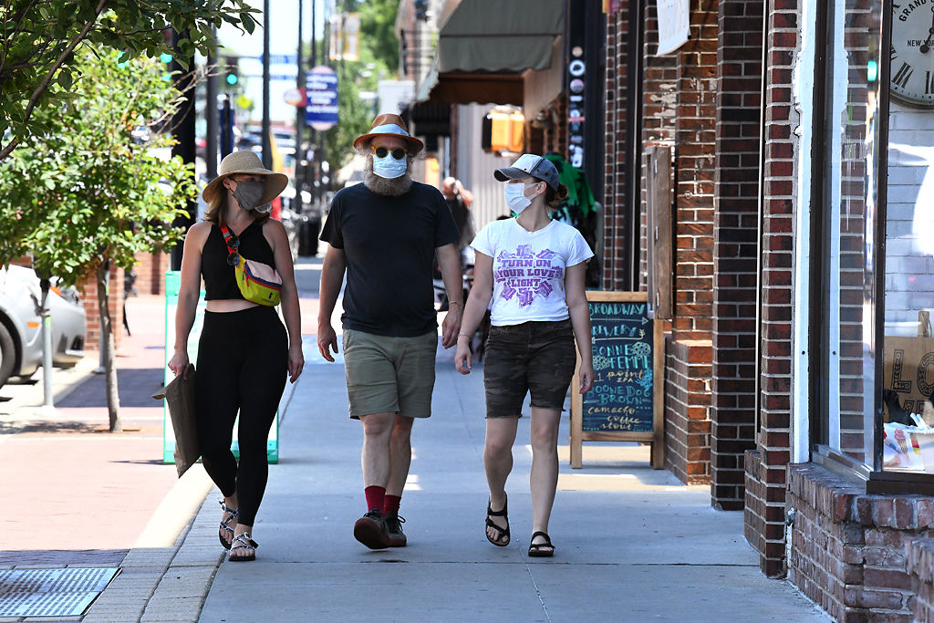 From left, Elizabeth Braaten Palmieri, Andy Grotelueschen, and Anna Sundberg don masks as they stroll down Broadway on Friday