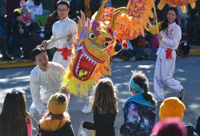 A member of MU's Confucius Institute plays with children at 2019 Homecoming Parade
