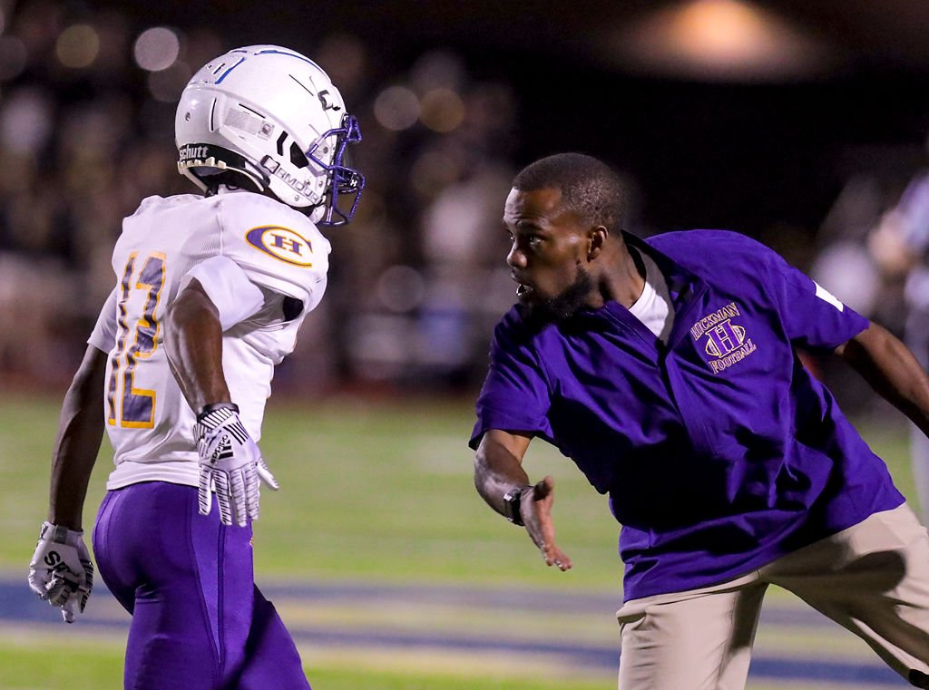 Hickman's head coach Cedric Alvis high fives La'Javion Williams