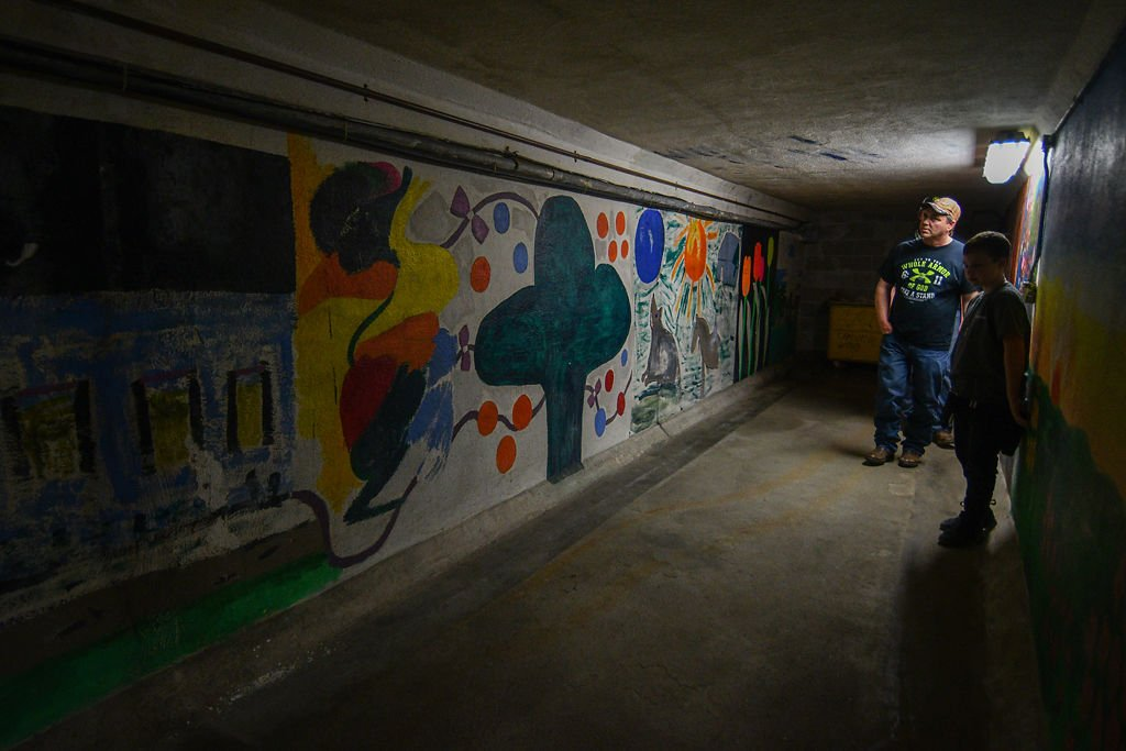 Visitors look at a mural painting in a tunnel