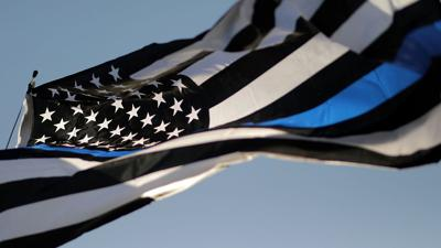 A 'Thin Blue Line' American flag waves above the finish line