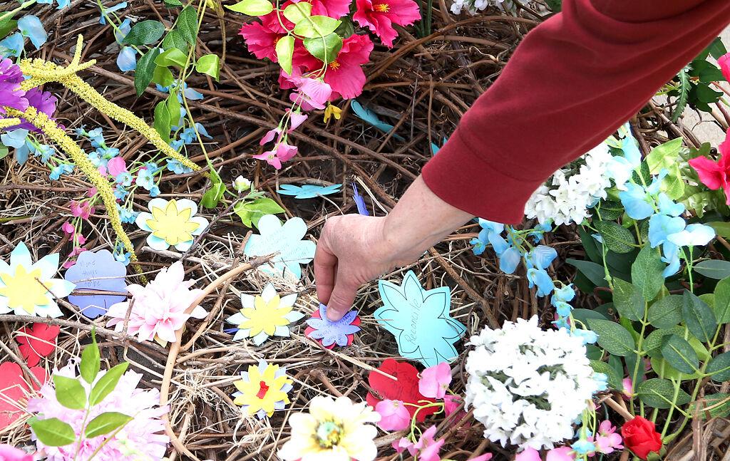 Jenn Muno places a paper flower into a collection basket