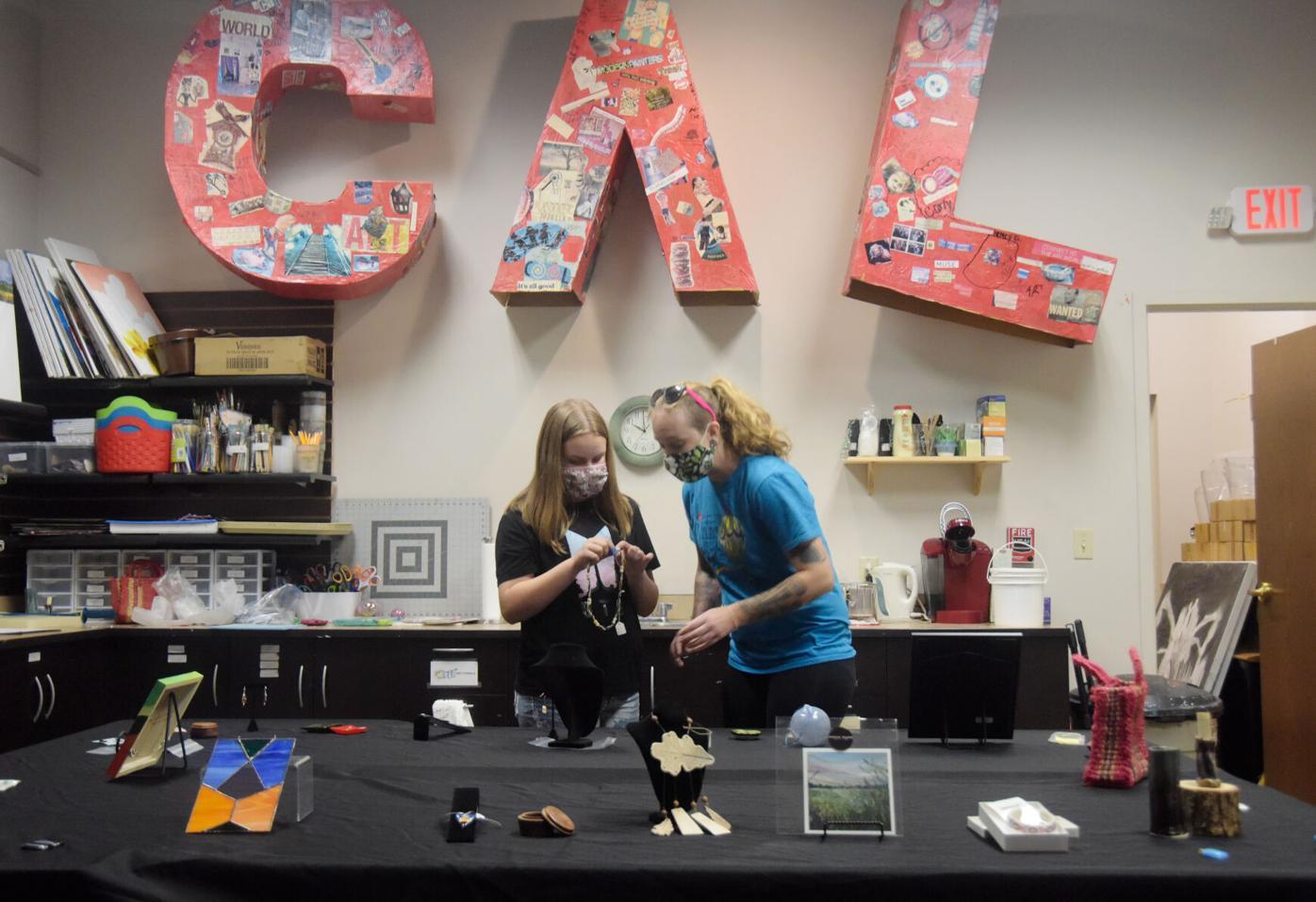 Leann Porrello helps Rebekah Fox pick out a piece of art