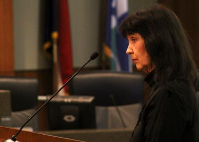 Sutu Forté stands silently at the podium during public comments