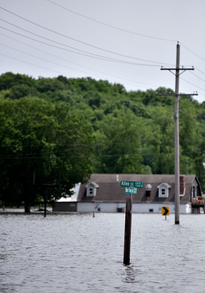 The sign at Allen Street and Burr Oak Road is seen among the rising water