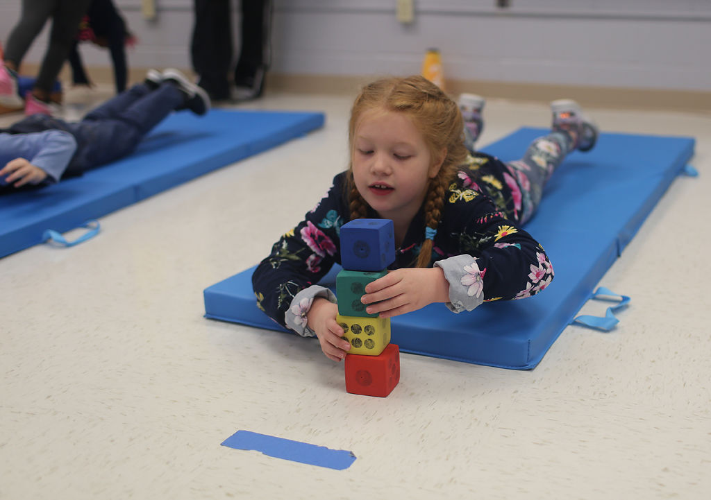 Zoe Stephens, 6, stacks blocks while doing a Superman pose during her motor lab class