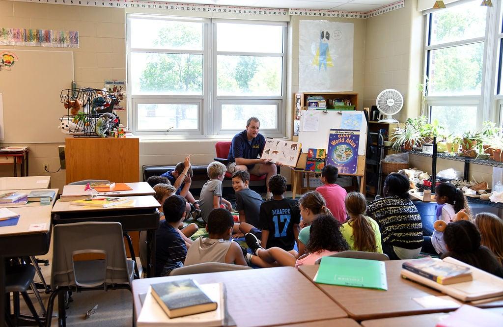 Fifth grade teacher Mr. Nies reads to his class