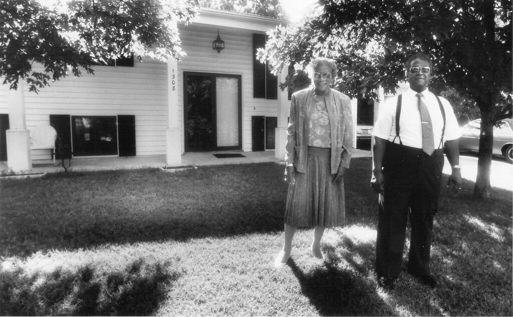 Clara and Earl Miles stand in front of their home