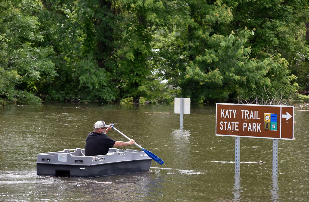 A resident of McBaine paddles through the flooded town