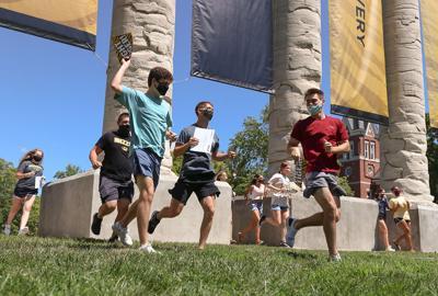 A group of MU freshman run through the columns for Tiger Walk