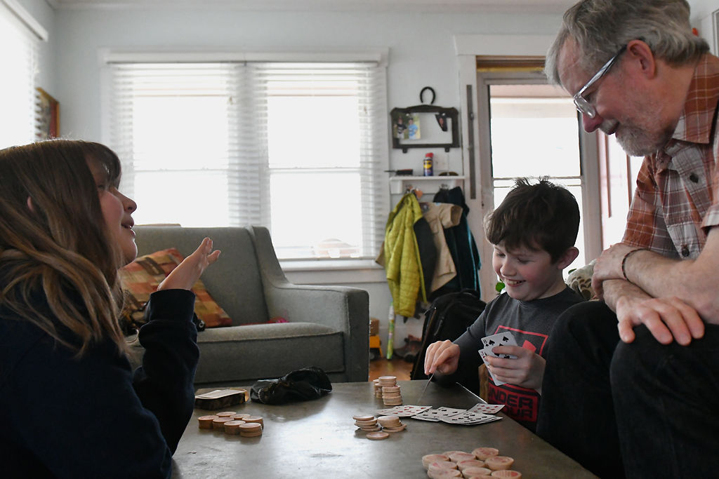 From left, Elizabeth, 13, Henry, 12, and their father Mike Odette play a round of poker